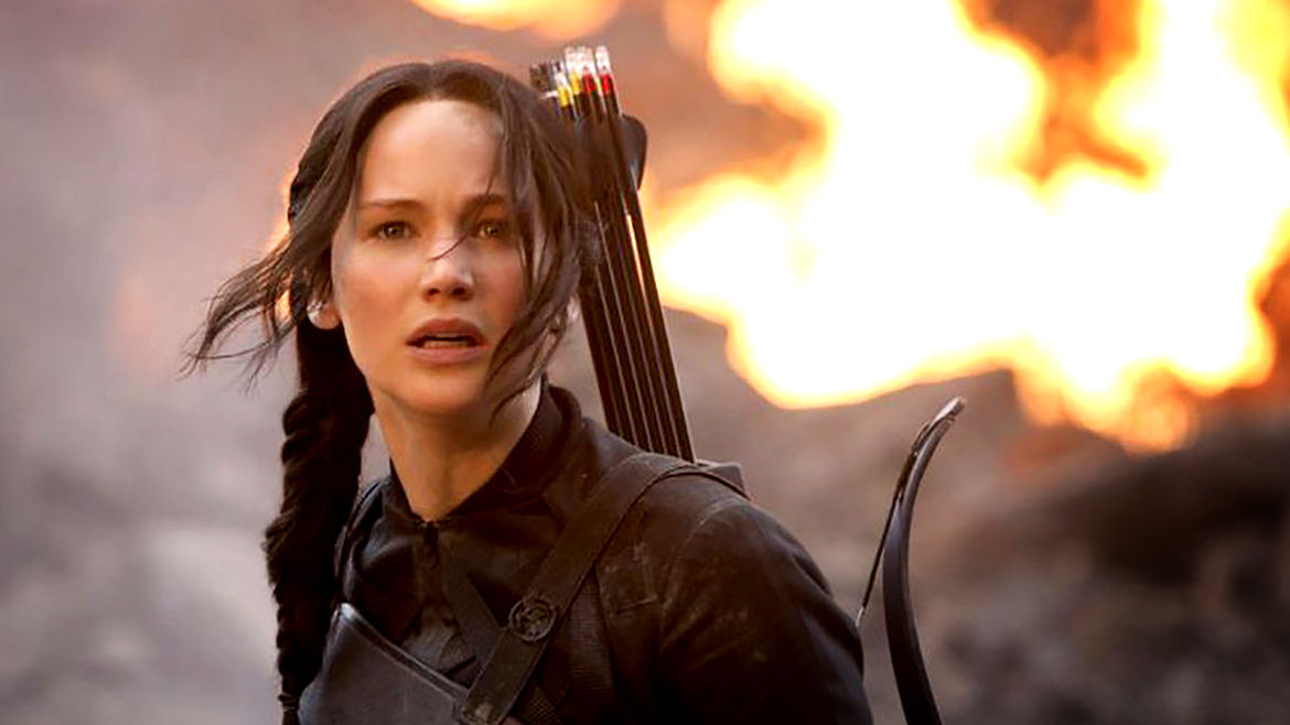 Cover Photo: An image from the film adaptation of The Hunger Games books: the protagonist Katniss standing among fires and rubble, looking distressed
