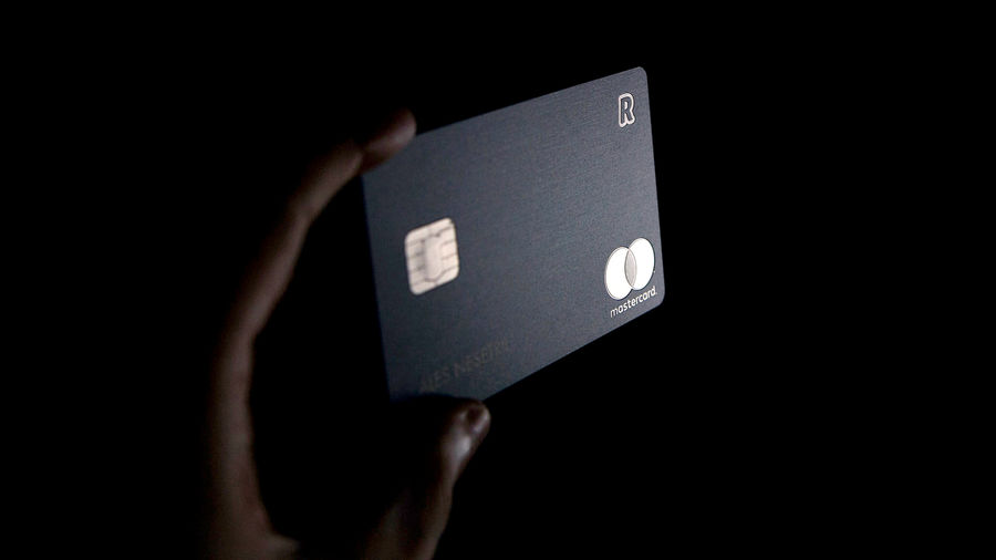 Cover Photo: An ominous photo of a black credit card being held in the dark, a light shining on the card's gold accents.