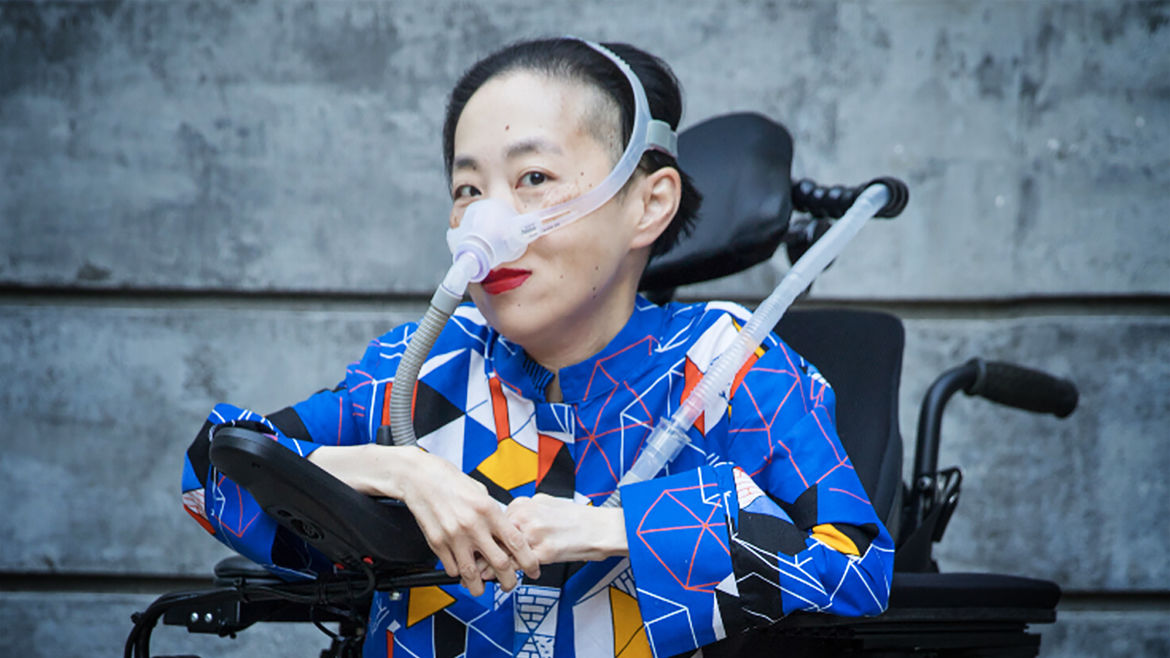 Cover Photo: A photo of the author, Alice Wong, looking into the camera. She is sitting in her wheelchair, wearing a blue shirt covered in a geometric pattern of yellow, orange, white, and black and her breathing apparatus. She is wearing red lipstick and smiling knowingly yet mysteriously at the reader.