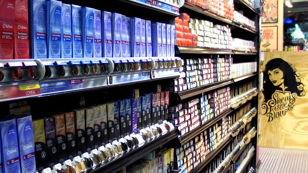 Cover Photo: An aisle of assorted L'oreal hair dyes, with hair samples in front of each color.