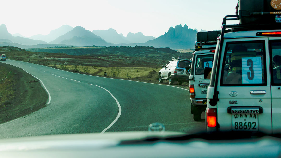 Cover Photo: An image of cars parked along the side of a road with mountains in the distance