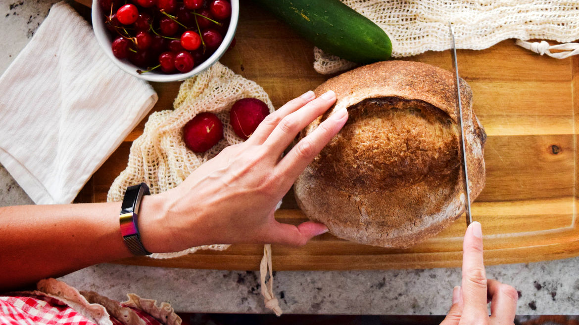 Cover Photo: An image of load of bread as someone cuts the bread with cherries in a bowl in the top corner