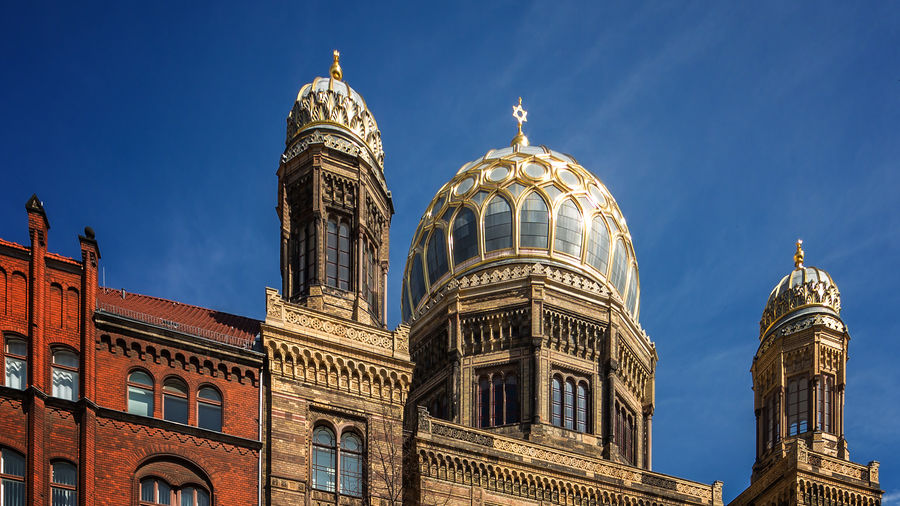 Cover Photo: This photograph shows a Berlin synagogue against a deep blue sky. The synagogue is built with sandy-colored bricks and the three towers are bright with gold detailing. A star of David stands up from the middle tower and serves as a small focal point for the center of the photograph