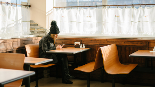 Cover Photo: A white woman sitting alone at a restaurant table in dark clothes, texting.