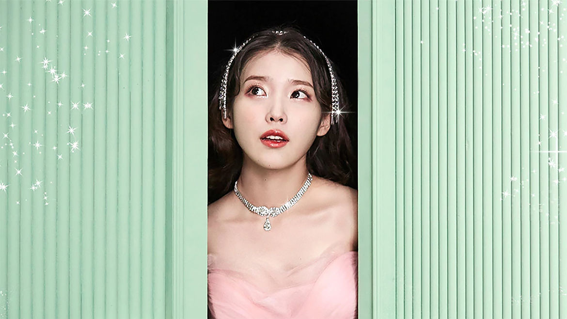 Cover Photo: IU, wearing a pink gown and a sparkling necklace and headband, gazing out from between pale green doors