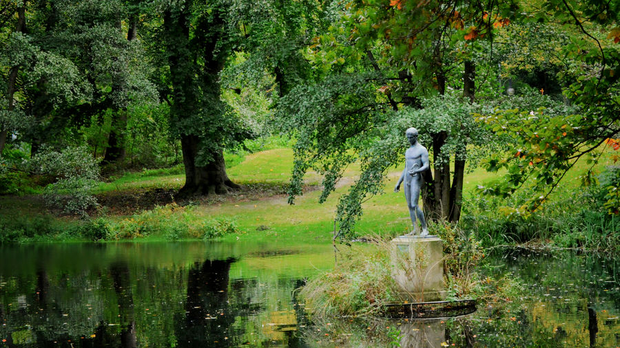 Cover Photo: In this photo of the Berlin park Tiergarten, we see bright leafy trees surrounding a peaceful, dark green pond. A coppery-green statue of a nude man holding an object (perhaps a piece of rope? perhaps a discus?), stares into the depths of the pond. The foliage is still green, but there are a few bright red leaves and the grass is starting to brown, as if we are reaching the end of a hot summer.