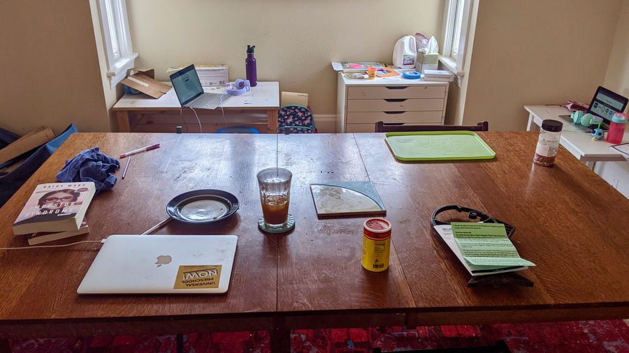 Cover Photo: photograph of a large wooden dining table with books, a laptop, a dish, a half-full glass, a green lunch tray, and other odds and ends on it; just behind, there's a smaller wooden desk and a small set of storage drawers; behind and to the right there is a small white desk—both desks also have laptops and headphones and various objects on top