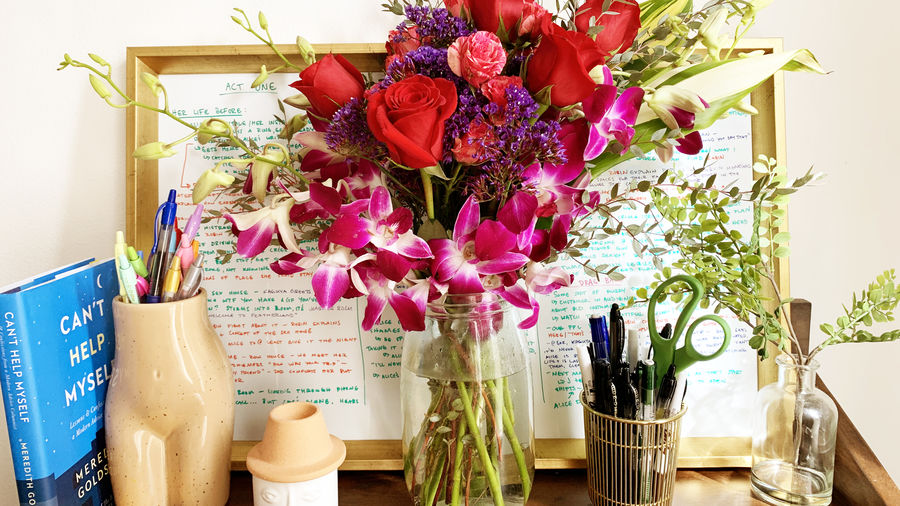 Cover Photo: A huge bouquet of flowers on a desk with writing utensils and a whiteboard with notes in erasable marker
