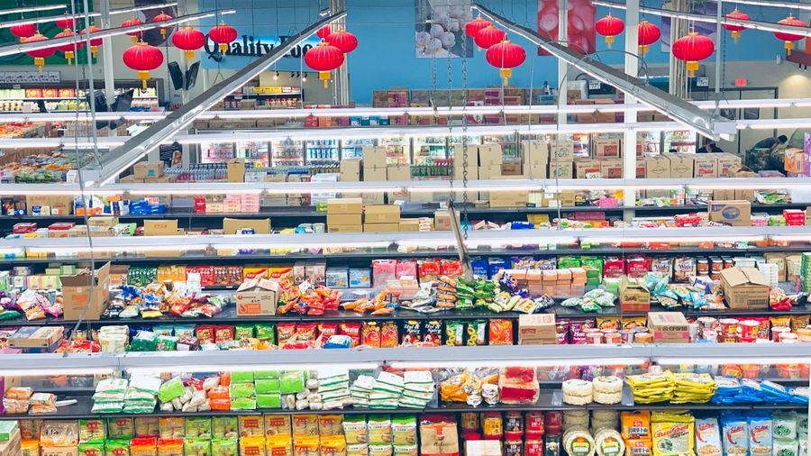 Cover Photo: In this photograph, we are looking down on the florescent aisles of a grocery store. We see rows of brightly colored food aisles and red Chinese tomato lights hanging down against a bright, sky blue wall at the end of the store.