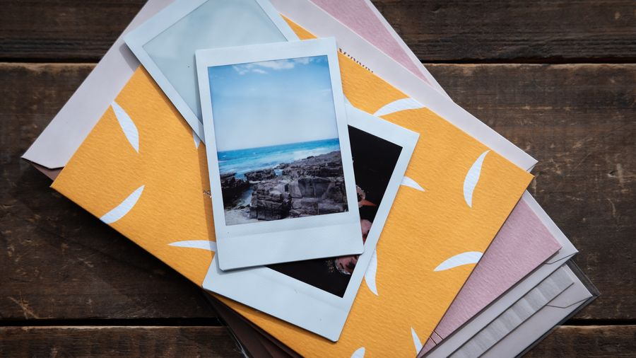 Cover Photo: In this photograph, we are looking down at a stack of pastel envelopes--white, pink, and yellow--with three polaroids stacked on top. The top image looks out to the ocean beyond a rocky shore. The table the stack of photographs and envelopes is sitting on is dark, worn wood.