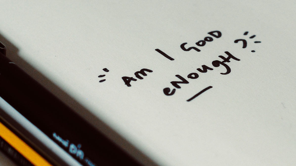 "Cover Photo: This photograph is a close up of a piece of white notebook paper. In handwriting, we see the phrase: ""Am I good enough?"" Enough is underlined for emphasis."
