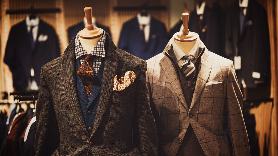 Cover Photo: Two mannequins well dressed in men's suits, with more department store suits visible in the background.
