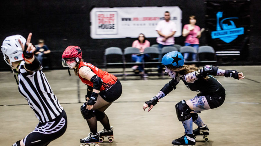 Cover Photo: This photograph shows two female roller derby skaters racing around the track. The woman in front wears red and the woman trying to catch her wears blue, including blue spotted face paint. The background is blurred, but in the front left we see a referee