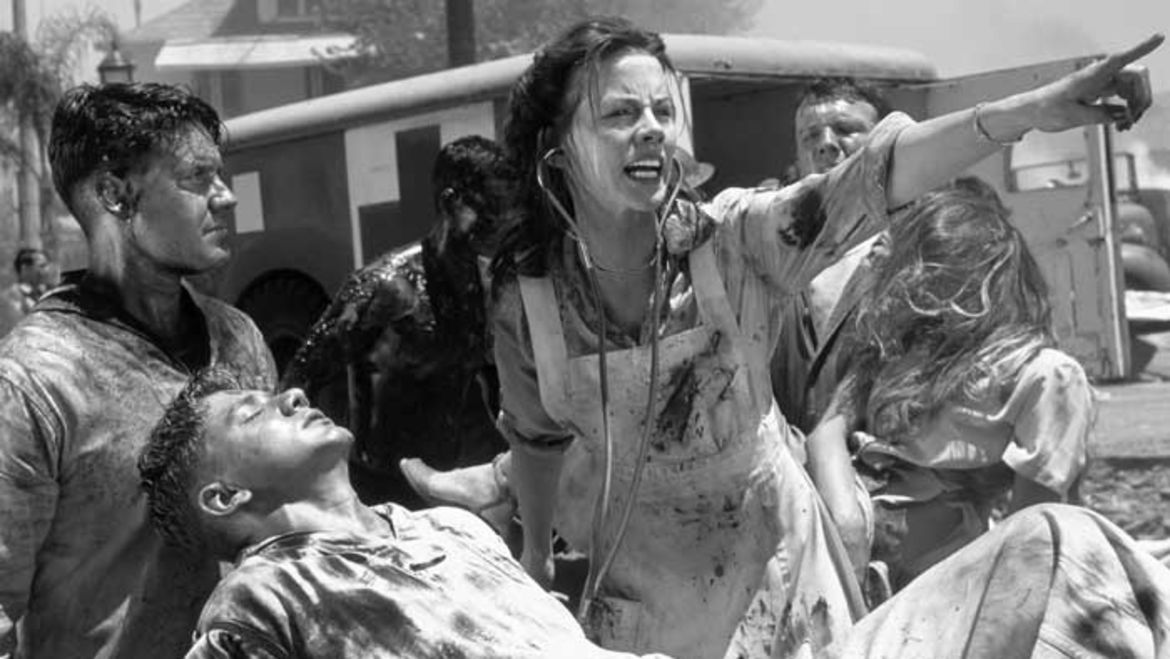 Cover Photo: This black and white image is a still taken from the 2001 movie, PEARL HARBOR. In it, we see one wounded soldier being propped up by his friend, while a nurse yells and points off into the distance.