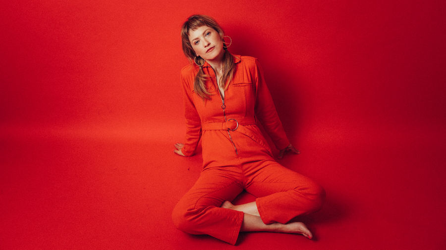 Cover Photo: This image is a photograph of the author. She wears a bright-red jumpsuit, hoop earrings, and her hair in loose ponytails. She sits cross-legged on the floor against a bright red background.