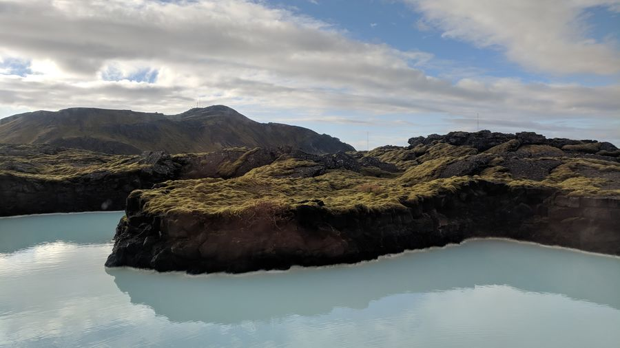 Cover Photo: This photograph shows a landmass, green and mossy, at the edge of a pale blue body of water. In the background, the blue sky is streaked with white clouds.