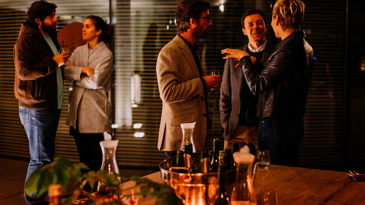 Cover Photo: A group of three men standing and talking in front of a candlelit dinnertable, and a man and woman talking over to the side. The lighting is dim and there are opened bottles on the table.