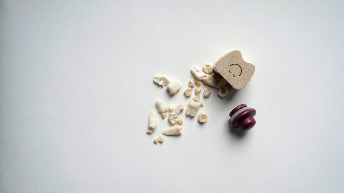 Cover Photo: A bunch of loose human teeth on a surface, spilling out of a small wooden container shaped like a cartoon tooth