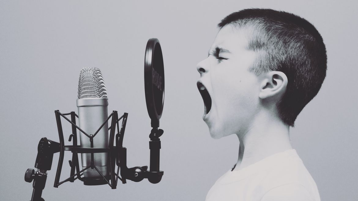 Cover Photo: In this black and white photograph, we see a young boy singing into recording equipment, including a microphone. His hair is buzzed short and his eyes are closed and his mouth as open, as if he is struggling to hit the right note