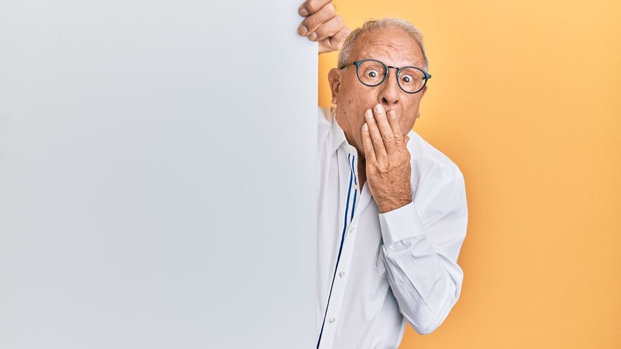Cover Photo: In this photograph, we see an older man peeking around the corner of a wall. He's wearing glasses and a white collared shirt. One hand is over his mouth and his eyes are open wide, as if shocked by what he is seeing.