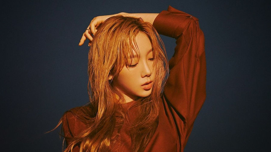 Cover Photo: photograph of Taeyeon in a long-sleeved burnt sienna dress against a dark blue background, head tilted to her left, eyes downcast, one arm extended up, hand resting on the back of her head