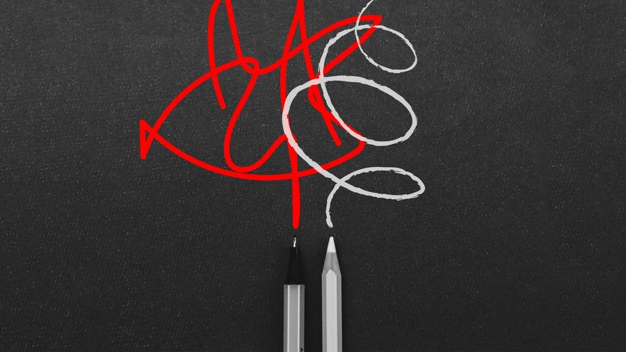 Cover Photo: This image has a dark background, almost the texture of a chalkboard. At the bottom, in the center, there is a silver pen and a white pencil. Coming out of the silver pen, we see angry red scribbles. Overlapping with the red, there are white loopy scribbles coming out of the white pencil