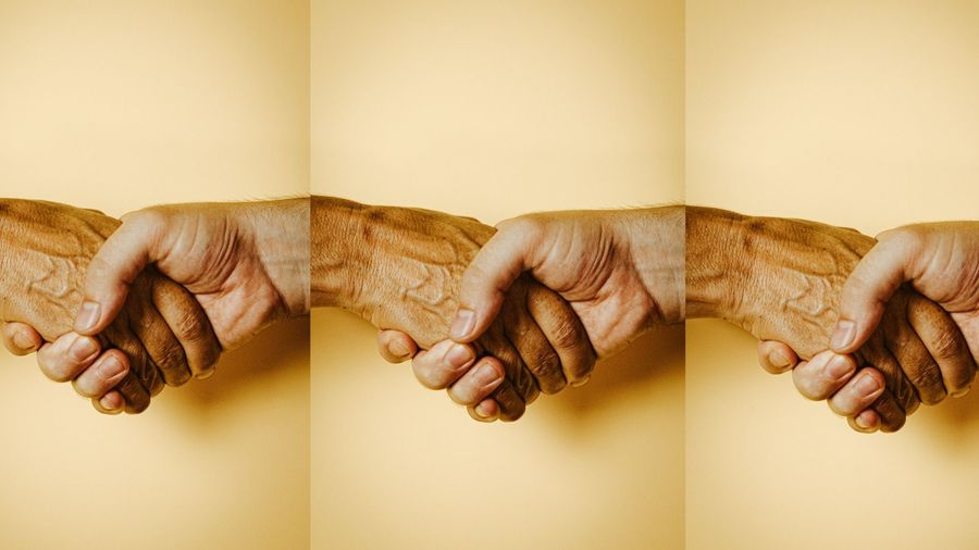 Cover Photo: We see a photograph of two hands shaking against a mellow yellow background. The hands look as if they might be older men and one hand is a few tones paler than the other. This photograph is showed three times in a row and the wrists connect at the end of the picture, as if part of a hand-shaking rope