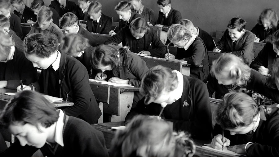 Cover Photo: historical black-and-white photograph of approximately two dozen white schoolchildren, writing with their heads bent over wooden desks