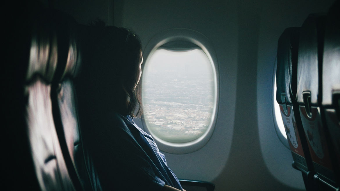 Cover Photo: An image of a woman who is traveling and she is looking outside of her window as she sits in an airplane.