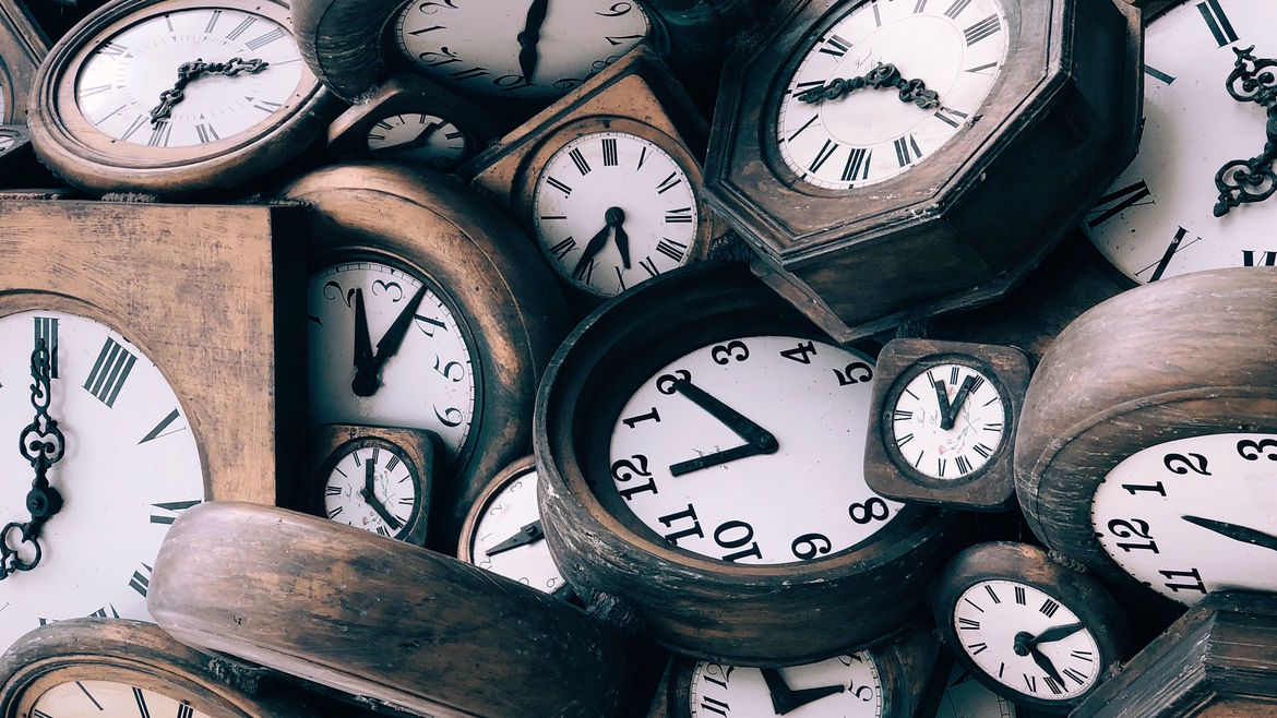 Cover Photo: This photograph looks down at a pile of clocks. Most of them have old wood around their faces and white faces with roman numerals and fancy hands. The pile feels a little unwieldy and overwhelming.