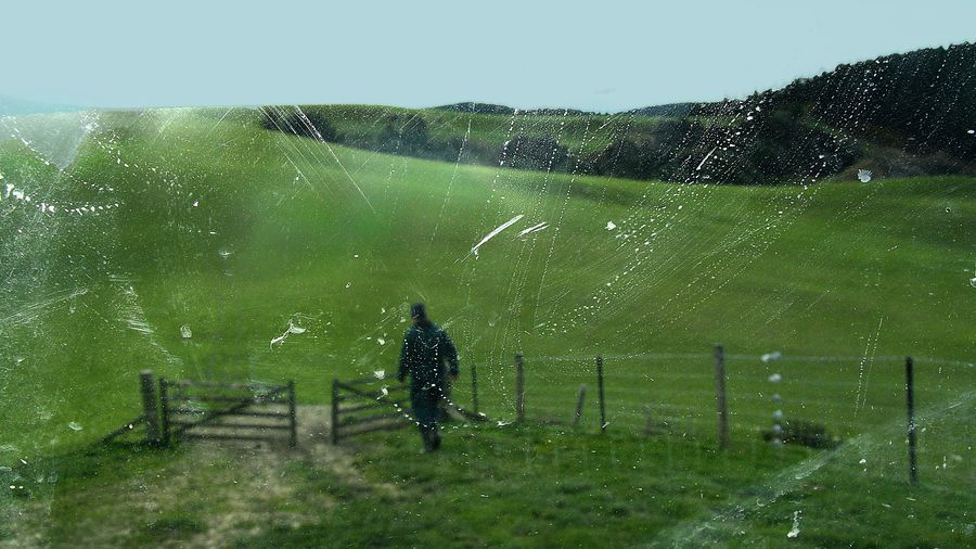 Cover Photo: A dirty truck window is in focus in this photo of a farmer at work with lush green hill country in the background. The farmer is walking toward an open gate.