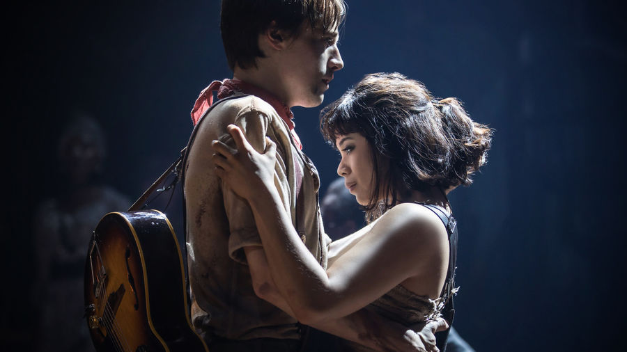 Cover Photo: A photograph of the musical Hadestown: a man in a woman embracing on a dark stage lit only by a spotlight