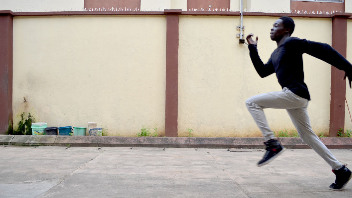Cover Photo: A Black boy in a black shirt, khaki pants, and black shoes running, coming in from the right of the frame. Behind him is a terracotta and cream-colored wall, with five blue buckets aligned against it.