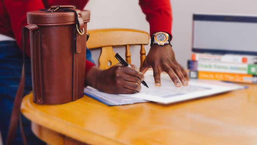 Cover Photo: This photograph shows a black man signing contracts on a table. He is wearing business casual clothes and a fancy leather bag sits on the table next to him.