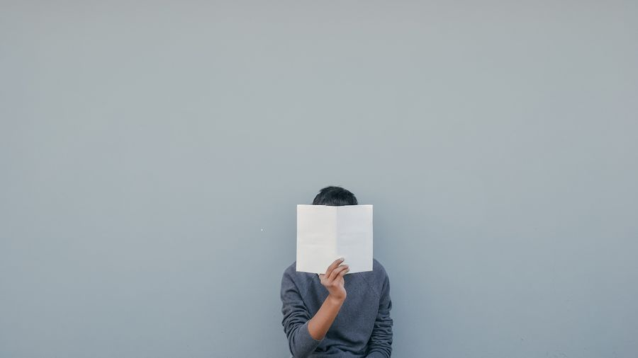 Cover Photo: This photograph shows someone wearing a gray sweater standing in front of a gray wall. With one hand, they are holding a blank white book open directly in front of their face.