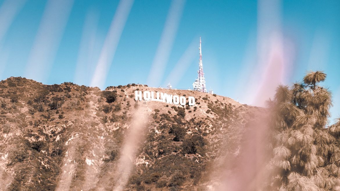Cover Photo: This photograph of the Hollywood sign is taken far down the hill and we're peering through dry grasses up at the brown hillside and bright blue sky