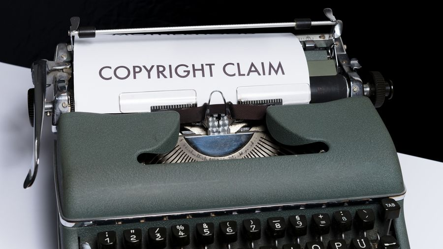 """Cover Photo: This photograph shows a green typewriter sitting on a white table. The paper scrolling out of the typewriter reads """"copyright claim"""""""