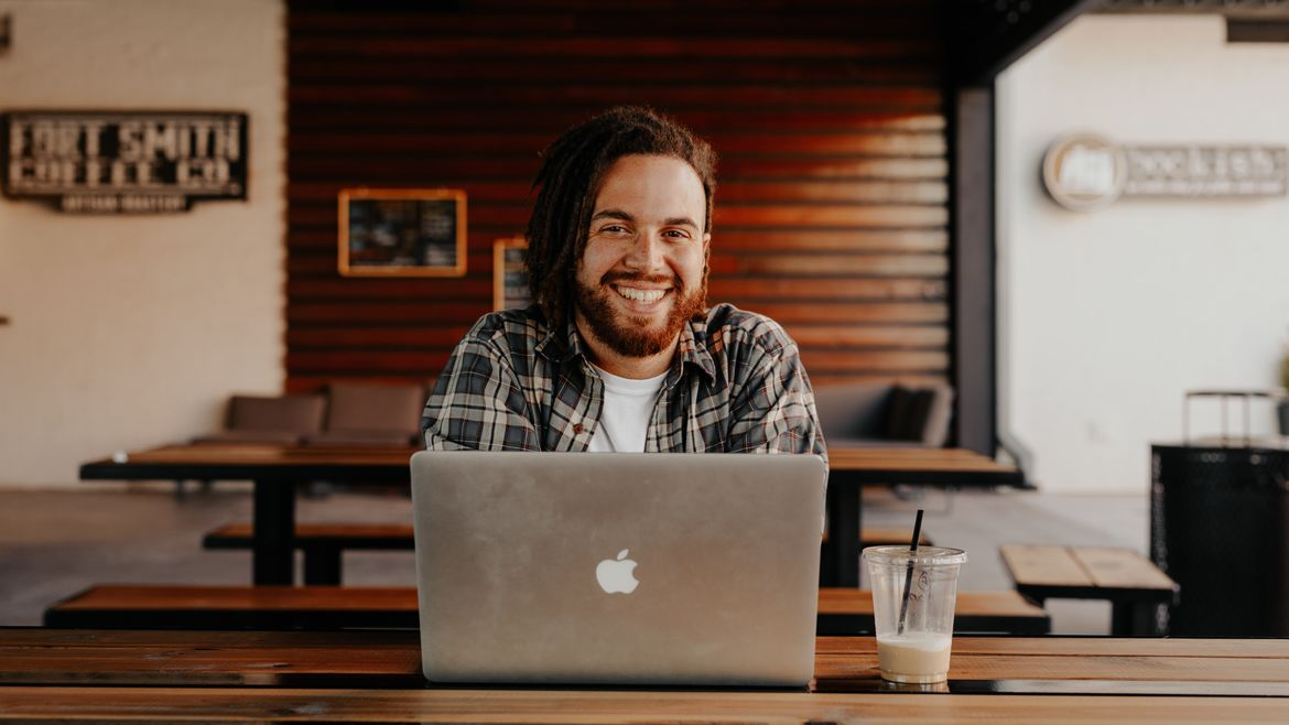 Cover Photo: A smiling man with reddish hair sits in a coffee shop with a laptop open in front of him. The picture looks warm and friendly.