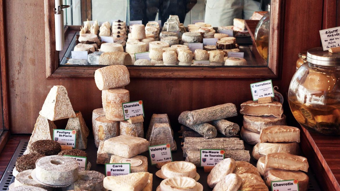 Cover Photo: In this photograph, we are looking  at a table filled with many kinds of soft cheeses. there is a mirror in the background that reflects the cheeses back at the viewer and the room is paneled in dark wood. Clear sunlight seems to be coming into the left side of the picture