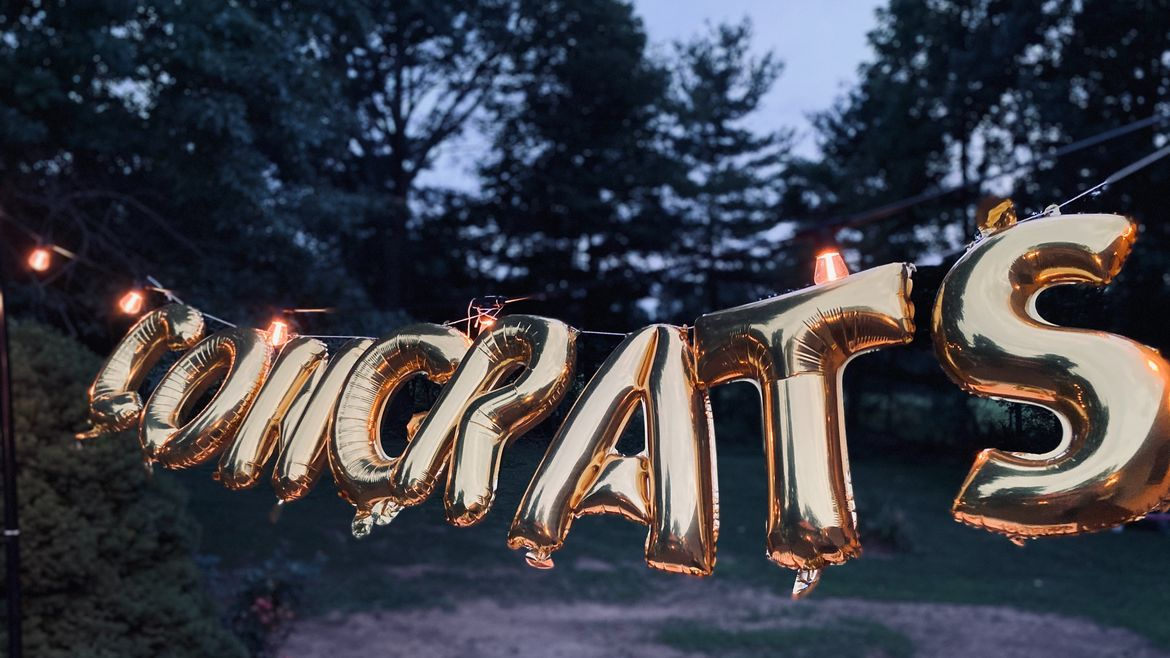 Cover Photo: This photograph shows a  gold balloon sign, which reads 'congrats,' blowing gently in an evening breeze