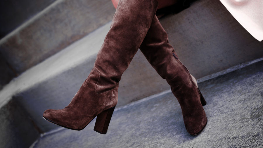 Cover Photo: A pair of brown suede knee-high boots, crossed at the legs by the wearer; they appear almost as if they are about to run