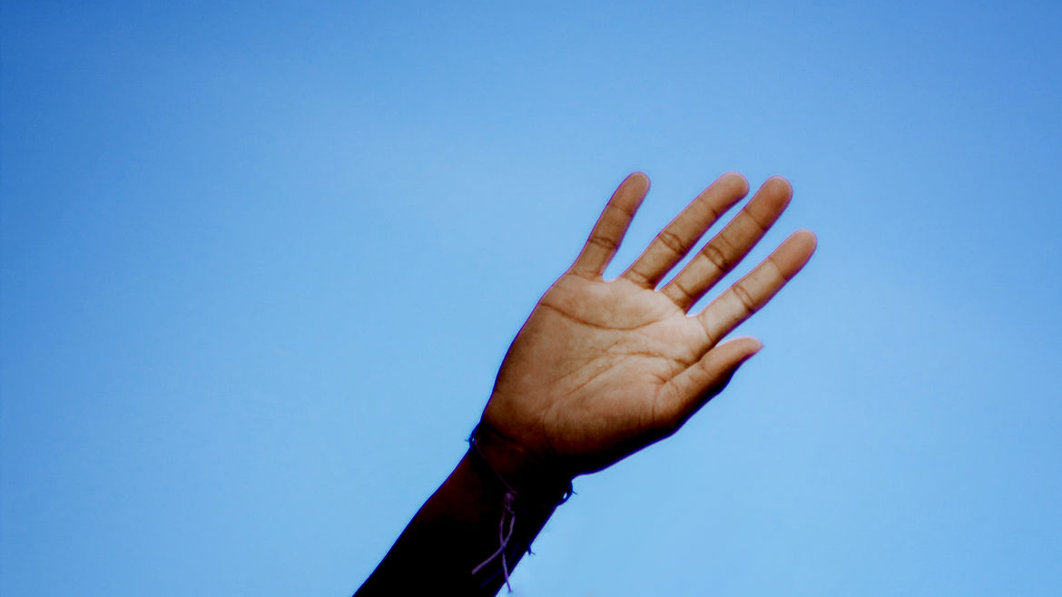 Cover Photo: a brown hand raised, waving against a background of blue sky
