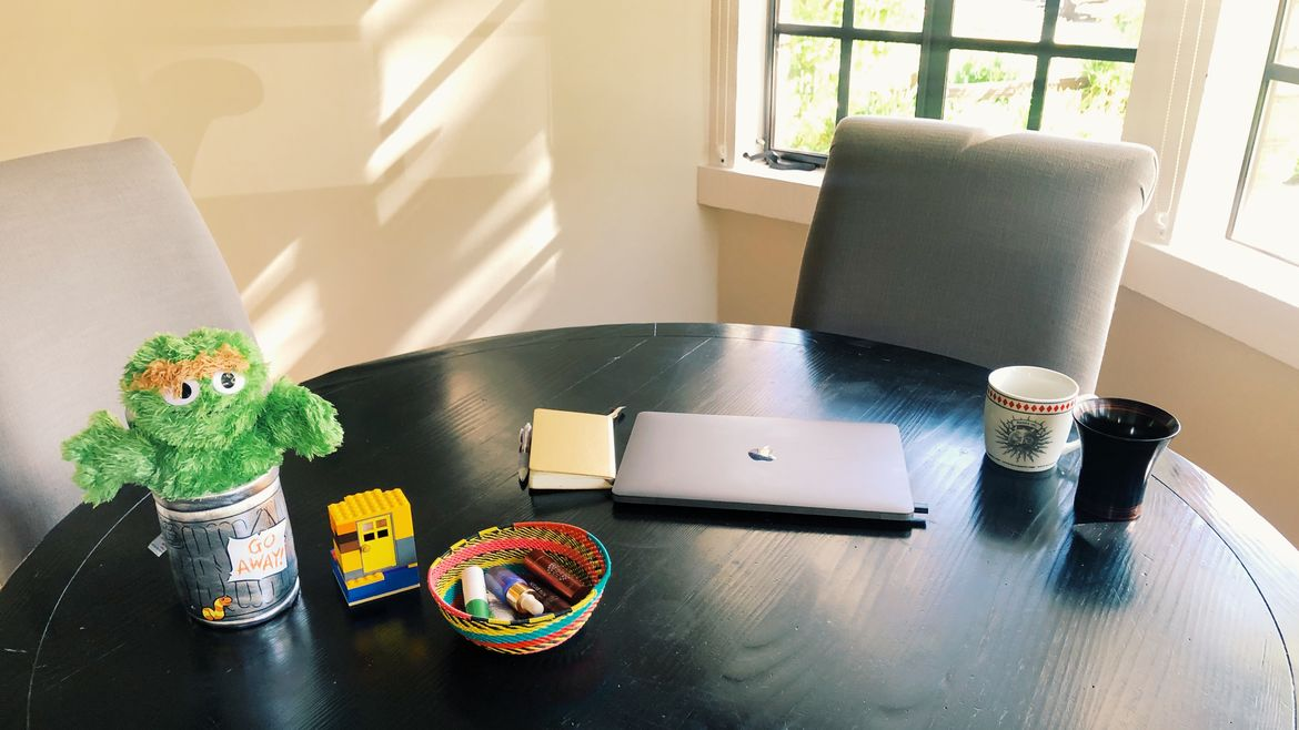 Cover Photo: This is a picture of Kathy Wang's kitchen table. The table is black wood and round; the chairs around the side are plush and gray. A window is propped open behind the table and yellowy light streams through against the cream walls. On the table, we see the author's laptop and the items she details in this essay.