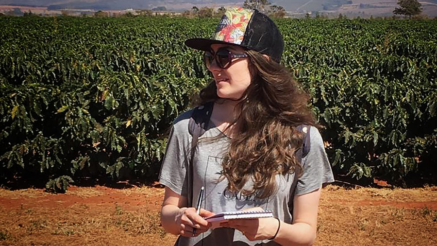 Cover Photo: A woman in a field of coffee plants wearing a hat and sunglasses takes notes