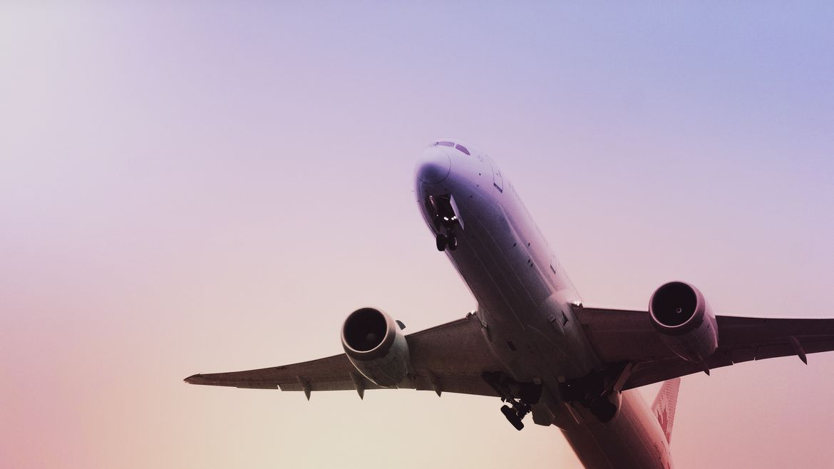 Cover Photo: This picture looks up at the belly of a plane as it takes off.  The sky is pale purple and yellow and red and these gentle sunrise colors are reflected on the plane.