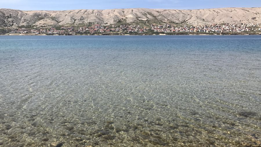 Cover Photo: This picture looks across a clear lake at the edge of an island. You can see scattered houses, though they are very tiny. Most of them look like they are white with reddish roofs. Behind them, brown hills rise up. We see a sliver of ocean behind.