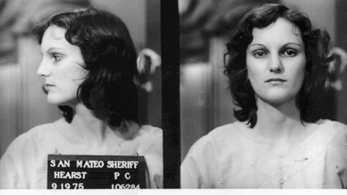 Cover Photo: Patty Hearst's mugshot from 1975. On the left, her face is turned so we can only see her profile. On the right, we are looking at her directly in her face. Her hair is dark brown and wavy, falling to her shoulders, and she has thin eyebrows arching above deep eye sockets