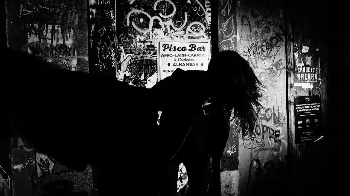 Cover Photo: This black and white photograph shows a dark shadowy figure tossing their hair against grimy, poster-strewn, and heavily graffitied walls.