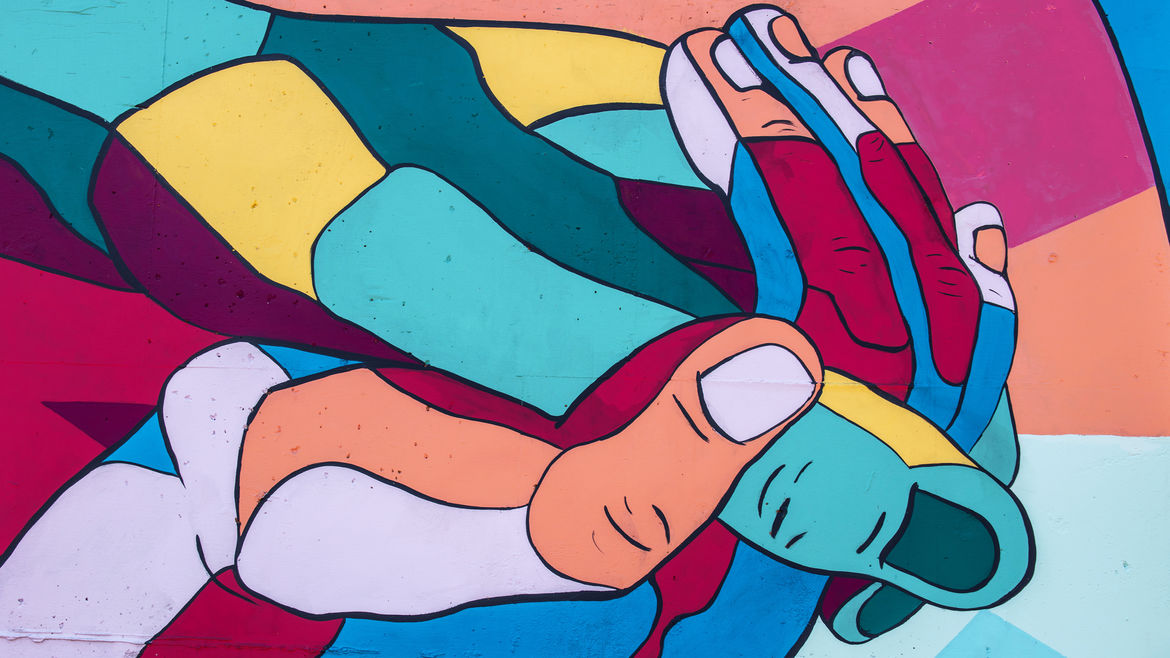 Cover Photo: An image of a mural of two hands in a rainbow of colors holding one another