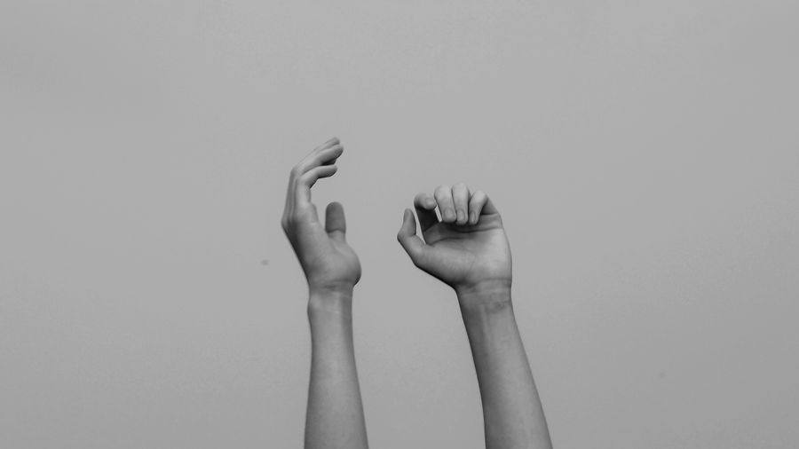 Cover Photo: In this black and white photograph, we see two pale-skinned arms reaching up from the bottom of the photo, as if stretching or reaching toward the sky.